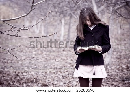 Young woman reading a book in the forest. - stock photo