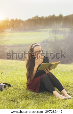 young woman reading a book in the nature - stock photo