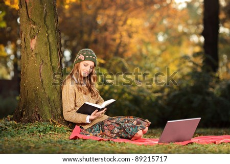 Young woman reading a book in the park - stock photo