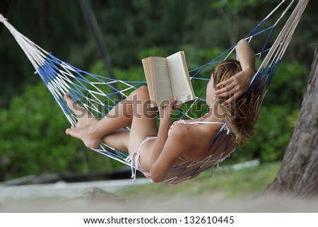 Young woman reading a book lying in a hammock on tropical sandy beach - stock photo