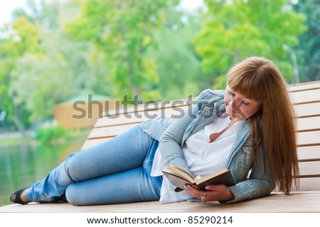 Young woman reading a book lying on the bench in the park