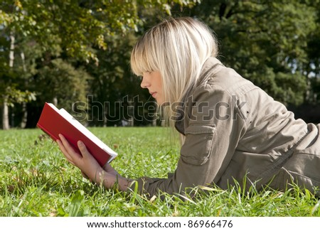 young woman reading a book on a meadow - stock photo