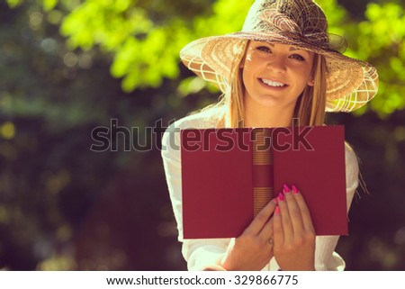 Young woman reading a book on a sunny summer day in the park - stock photo