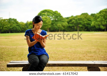 young woman reading a book on the bench in the park - stock photo