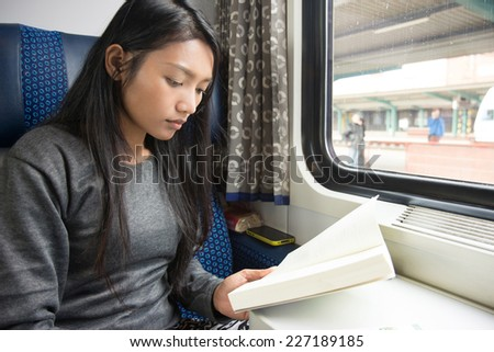 Young woman reading a book on the train - stock photo