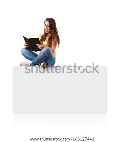 young woman reading a book sitting on a white box