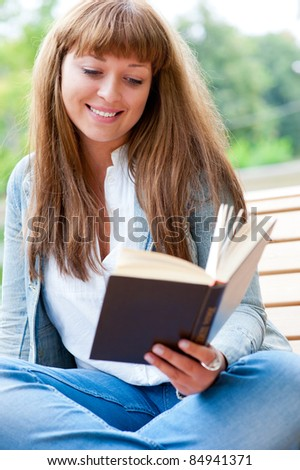 Young woman reading a book sitting on the bench in the park