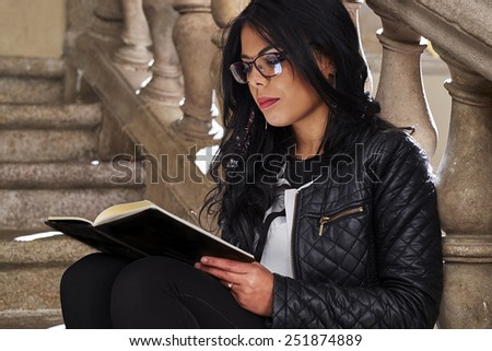 Young woman reading a book sitting on the stairs