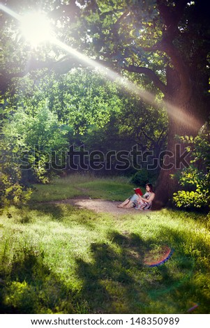 Young woman reading a book under the tree illuminated by rays of evening sunlight  - stock photo