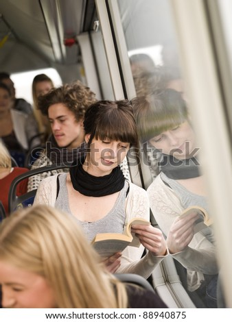 Young woman reading a book while going by the bus - stock photo