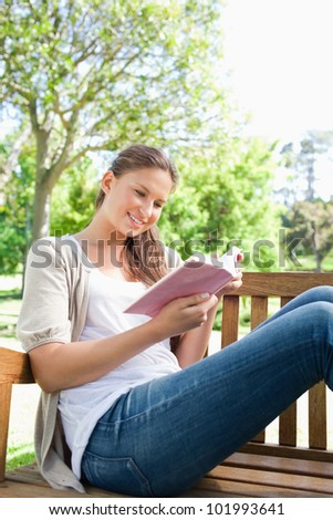Young woman reading a book while sitting on a bench