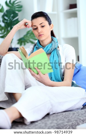 Young woman reading  a boring book, tired student at home