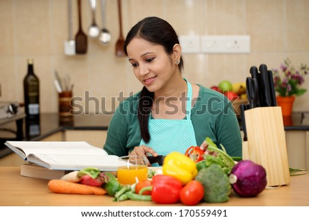 Young woman reading a cook book in her kitchen - stock photo