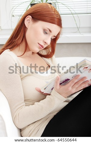 Young woman reading a magazine at home - stock photo