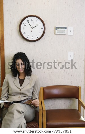 Young woman reading a magazine in waiting room - stock photo