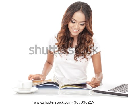 young woman reading a magazine while having a cup of tea in the morning isolated on white background