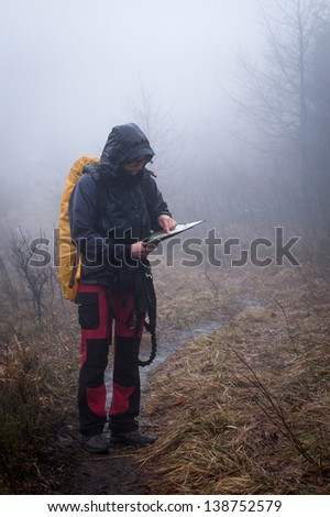 Young woman reading a map in the misty evening - stock photo