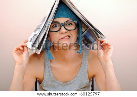 Young woman reading a newspaper - stock photo