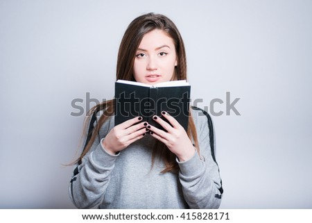young woman reading a notepad, close-up isolation on gray - stock photo