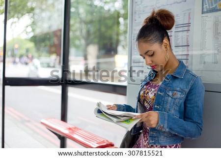 young woman reading a paper at the bus stop - stock photo