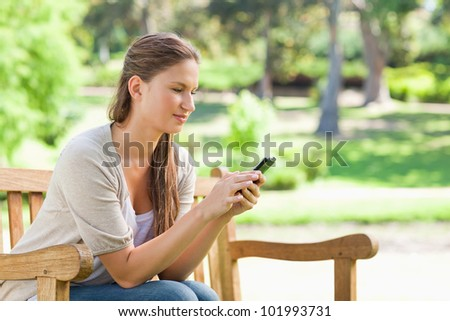 Young woman reading a text message on a park bench