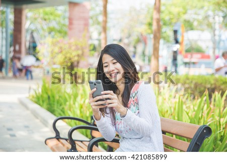 Young woman reading a text message on a park bench - stock photo
