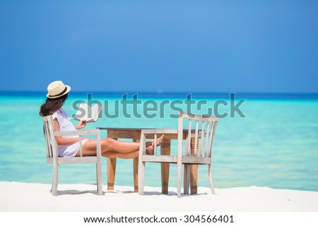 Young woman reading at outdoor beach cafe