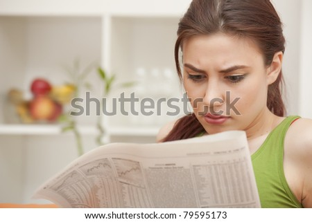 young woman reading bad news in newspaper at home - stock photo