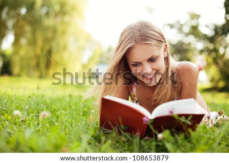 Young Woman reading book at park lying down on grass. Selective focus