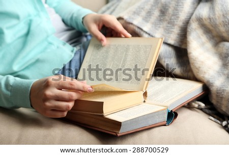 Young woman reading book, close-up, on home interior background - stock photo