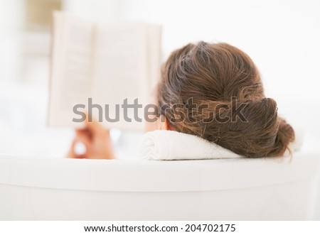 Young woman reading book in bathtub. rear view - stock photo