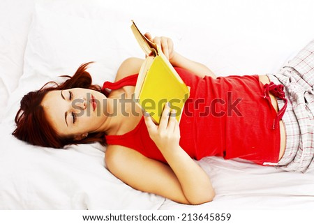 Young woman reading book in bed. Isolated on white background. - stock photo