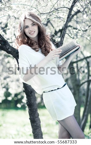 Young woman reading book in summer park. Bright white colors. - stock photo