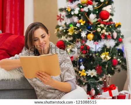 Young woman reading book near Christmas tree - stock photo