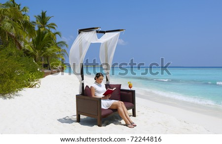 Young woman reading book on the beach - stock photo