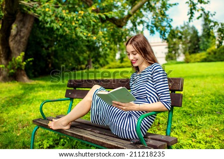 Young woman reading book on the bench smiling and happy. Pretty young woman enjoying spring in the park. - stock photo