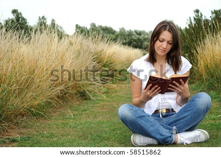 Young woman reading book outdoor - stock photo