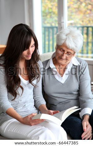 Young woman reading book to elderly woman - stock photo