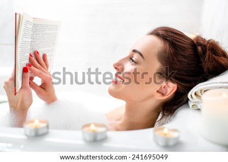 Young woman reading book while lying in the bath with foam and candles - stock photo