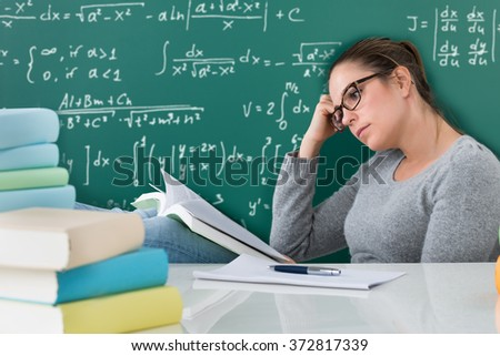 Young Woman Reading Books At Desk In Classroom
