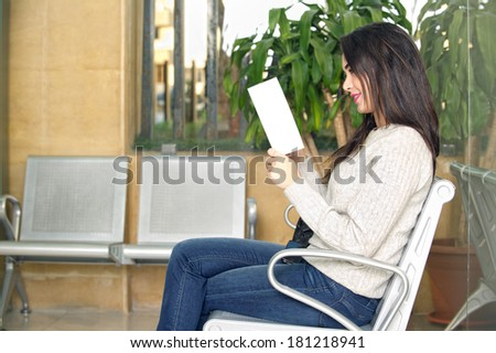 young woman reading brochure in doctor's waiting room  - stock photo