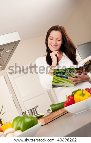 Young woman reading cookbook in the kitchen, looking for recipe - stock photo