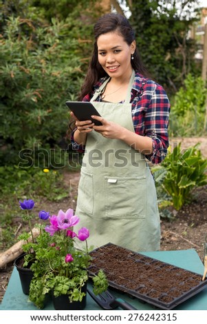 young woman reading gardening instructions on her tablet