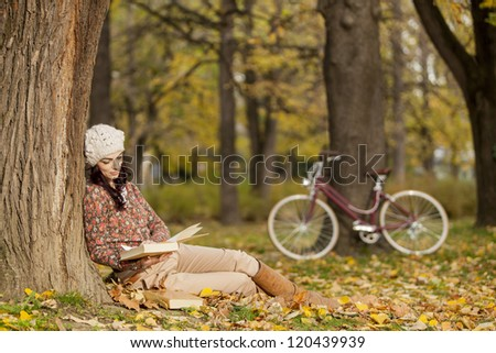 Young woman reading in the autumn forest - stock photo