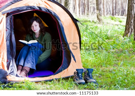 Young woman reading in the middle of the forest - stock photo