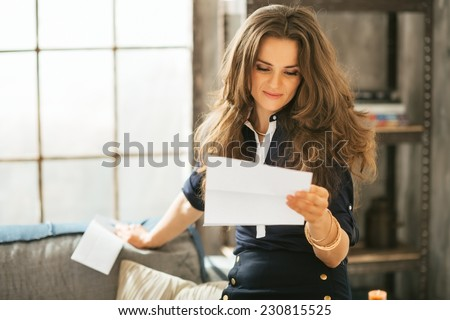 Young woman reading letter in loft apartment - stock photo