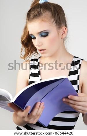 Young woman reading magazine. - stock photo