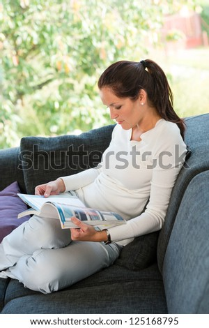 Young woman reading magazine living room couch sofa - stock photo