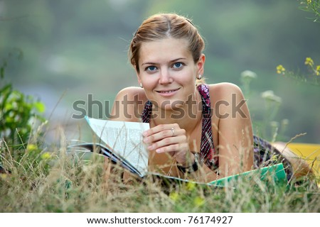 Young woman reading magazine lying on grass - stock photo