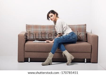 young woman reading magazine on sofa  - stock photo